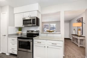 Renovated Kitchen with White Tile Backsplash and Stainless Steel Appliances