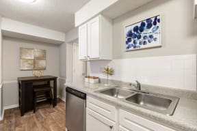 Renovated Kitchen with White Cabinets and Light Grey Countertops with High Top Table in the Dining Room