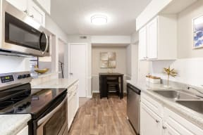Renovated Kitchen with Stainless Steel Appliances, White Cabinets and Wood Style Flooring