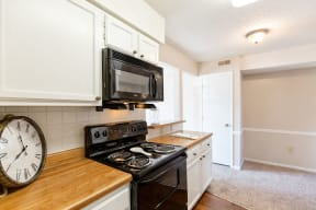 Classic Kitchen with White Cabinets, Black Appliances and Butcher Block Counters