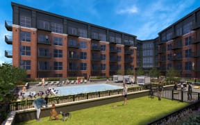 Maple Street Lofts Fenced-in Bark Park with Grass Turf Next to Pool and Outdoor Game Area