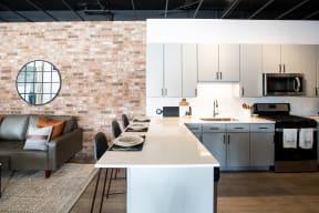 Maple Street Lofts Modern Kitchen with Open Layout, Hardwood Floors, Subway Tile Backsplash, and Breakfast Bar Counter