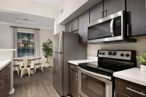 Apartment home with espresso cabinetry and stainless steel appliances| Lodge at Lakeline Village