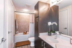 bathroom with espresso cabinets, white countertops and bath shower combo