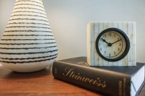 bedside table with book, clock and vase