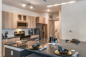 Coda Orlando's kitchen with hard flooring, wooden cabinets, and stainless steel appliances in Orlando, FL