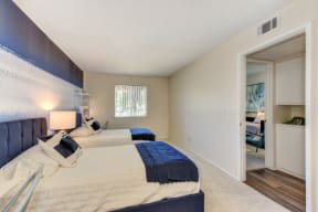 Bedroom with 2 twin beds with blue and white bedding.  Washer and dryer visible in hallway