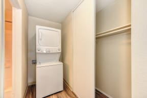 Stackable washer and dryer inside apartment with closet to the right and Hardwood Inspired Floors