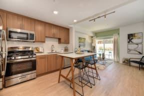 Model home kitchen with stainless steel appliances and dining room table.  Hardwood inspired flooring flows into the living room from the kitchen