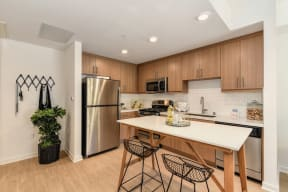 Model home kitchen with stainless steel appliances, hardwood inspired flooring and light brown cabinetry