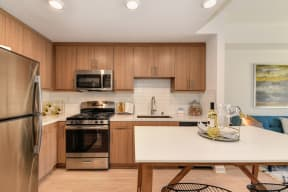 Model home kitchen with stainless steel appliances and light brown cabinetry