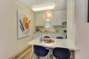 Dining area with white counters and two blue chairs overlooking the kitchen. White cabinets and appliances in the kitchen