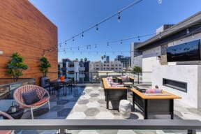 Community rooftop lounge area in the afternoon.  Area is equipped with chairs, couches, flat screen TV mounted on the wall and views of the city