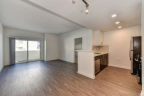 Vacant apartment living room with hardwood inspired flooring and views of the kitchen