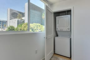 Washer and dryer inside of a closet. Door to washer/dryer is open and window shows views of outside.