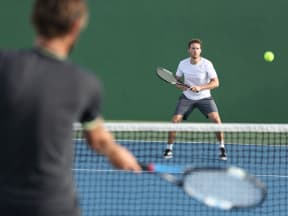 two young men playing tennis