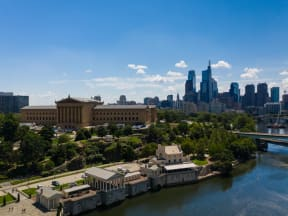 the Philadelphia Water Works and Philadelphia Museum of Art next to the river with the skyline behind it
