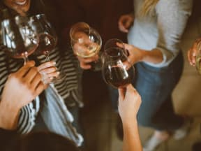 Close up of a group of females cheering each others wine glasses.