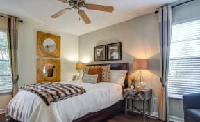 Bedroom with wood like style flooring, drapery, bed, nightstands, arm chair, table lamps, ceiling fan & wall art.