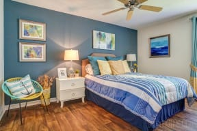 Bedroom with two nightstands, bed, ceiling fan, wall art, corner chair and wood style flooring.