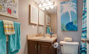 Bathroom with nautical style wall photos, white toilet, white sink tan tiled shower and dark brown cabinets.
