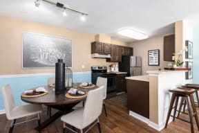 Kitchen with dark brown cabinets, stainless steel appliances, round dark table and light gray chairs.