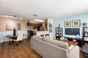 Living room with gray couch, wall mounted TV and kitchen/dining area in background with wood style floors.