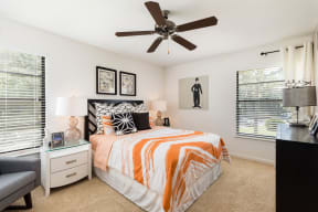 Bedroom with carpet, white nightstand, bed with white and orange bedding and ceiling fan.