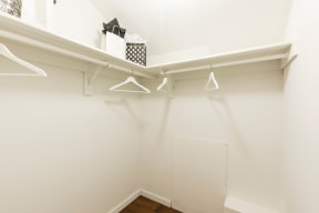 Walk-In closet with hangers handing from shelves.