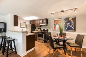 Kitchen and dining area with dark brown cabinets, stainless steel appliances and circle table with chairs.