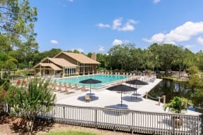 Pool deck with lounge chairs, tables, umbrellas, pool, trees and club house in the background.