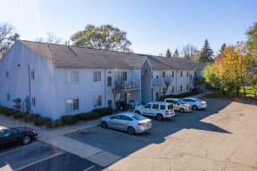 Exterior of Greyberry Park Apartments with parking lot with cars.