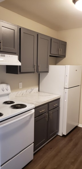 Grey cabinets with white and grey coutnertops, a white stove, and white fridge, and dark hardwood-like flooring.