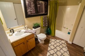 City Edge Flats Spacious Bathroom with Shower Tub, Vanity with Storage, and Wood-Style Floors