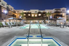 Outdoor pool and jacuzzi area with lounge chairs