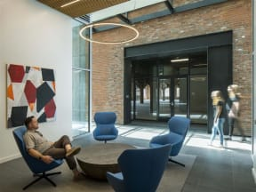 Lounge Area with Four Blue Chairs Circled Around a Coffee Table in Co-working Building With Modern Art Decor at 10 Clay Apartments in Seattle, Washington