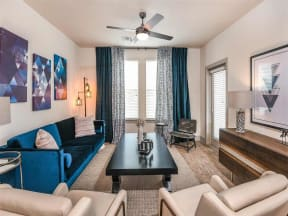 Furnished living room with carpet flooring and access to private patio in Coda Orlando apartments in Orlando, FL