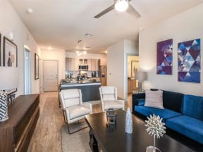 Furnished living room with wood floors and access to kitchen in Coda Orlando apartments in Orlando, FL