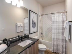Spacious bathroom with toilet and bathtub in Coda Orlando apartment rentals in Orlando, FL