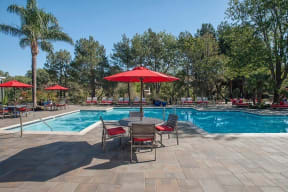 Pool with table and chairs Apartments in Pittsburg, CA l Kirker Creek Apartments