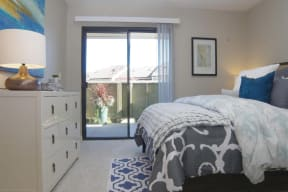 Bedroom with patio door Apartments in Pittsburg, CA l Kirker Creek Apartments
