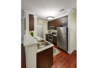 Kitchen with stainless steel appliances; door to laundry area