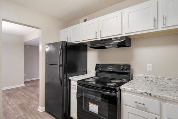 renovated kitchen, white cabinets, black appliances, grey brown wood style flooring