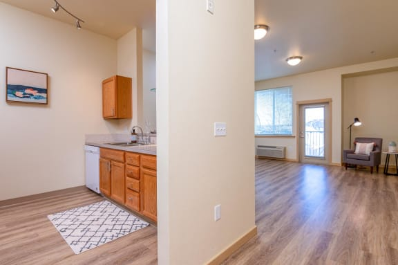 Split view of kitchen and living room. Beautiful wood like flooring throughout. Large pass through window from kitchen to living room.