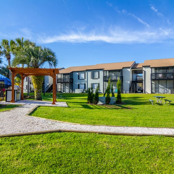 apartment buildings in Jacksonville with landscaping and grilling area