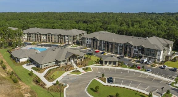 Welcome to The Retreat at Fairhope Village in Fairhope, AL. The community features a large entry drive, leasing center building, pool, and residential buildings.