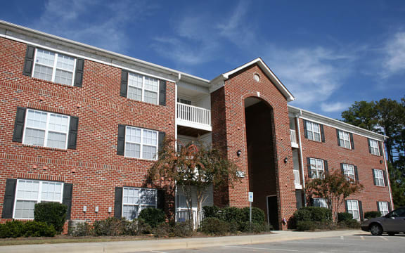 Exterior of red brick three-story apartment building at Crescent Commons in Fayetteville, NC