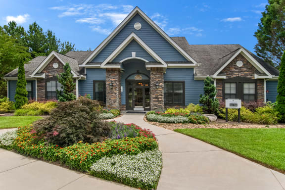 Resident clubhouse exterior with lush landscaping at Heritage at Riverstone apartments in Canton, GA