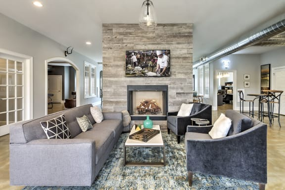 Clube house at The Retreat at the Park in Burlington, NC furnished with a couch and chairs in front of the fireplace