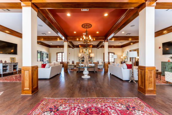 Interior of the resident clubhouse and leasing center with grand entry, sofas, TVs and fireplace at Riverstone apartments for rent in Macon, GA